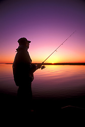 Stock photo of the silhouette of a man fishing in the bay at sunset