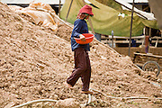 30 JUNE 2006 - PHNOM PENH, CAMBODIA: A worker walks down a pile of mud at a brick factory in Phnom Penh, Cambodia. According the United Nations Food and Agricultural Organization, there are more than 70 brick factories in Phnom Penh and its environs. Environmentalists are concerned that the factories, most of which burn wood in their kilns, contribute to deforestation in Cambodia. They are encouraging factory owners to switch to burning rice husks, as brick kilns in neighboring Vietnam do. The brick factories are kept busy feeding Phnom Penh's nearly insatiable appetite for building materials as the city is in the midst of a building boom brought by on economic development and the need for new office complexes and tourist hotels.   Photo by Jack Kurtz / ZUMA Press