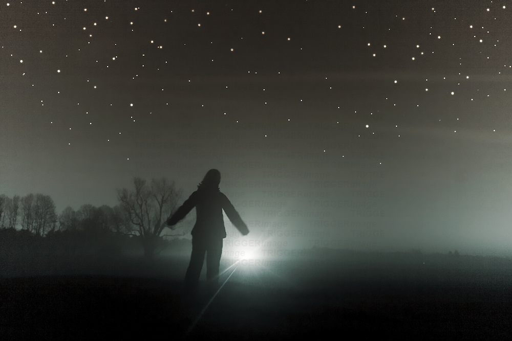 A silhouetted figure standing in a field with a bright light in the distance