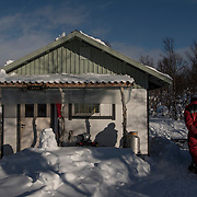 """""""It took 12 days to build this cabin. We had three roofing ceremonies and two """"savuviinat"""" (celebration for the first smoke from the chimney)."""" Says gold miner Tauno Leino in Lemmenjoki wilderness area."""