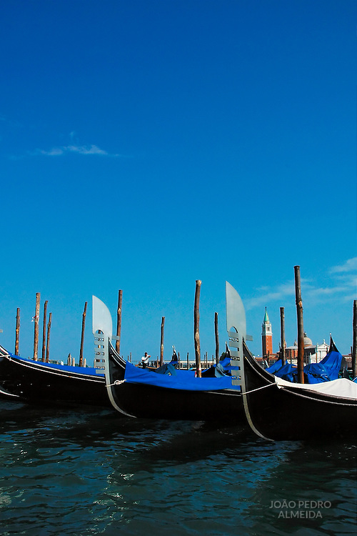 Anchored gondolas in Venetian lagoon with tower in the background