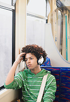 Young Man sitting Listening to Headphones on Commuter Train