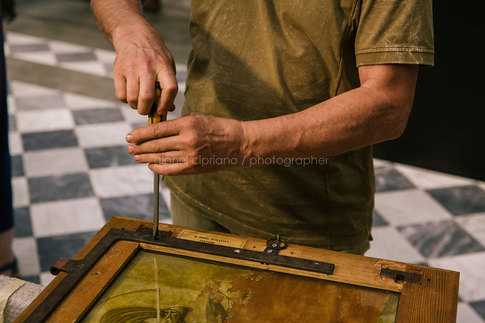 FLORENCE, ITALY - 3 JUNE 2018: A techinician unscrews the frame containging Raphael's portrait of Agnolo Tondi, here at its new location  in room 41at the Uffizi, in Florence, Italy, on June 3rd 2018.<br /> <br /> As of Monday June 4th 2018, Room 41 or the &ldquo;Raphael and Michelangelo room&rdquo; of the Uffizi is part of the rearrangement of the museum's collection that has<br /> been defining Uffizi Director Eike Schmidt&rsquo;s grander vision for the Florentine museum.<br /> Next month, the museum&rsquo;s Leonardo three paintings will be installed in a<br /> nearby room. Together, these artists capture &ldquo;a magic moment in the<br /> first decade of the 16th century when Florence was the cultural and<br /> artistic center of the world,&rdquo; Mr. Schmidt said. Room 41 hosts, among other paintings, the dual portraits of Agnolo Doni and his wife Maddalena Strozzi painted by Raphael round 1504-1505, and the &ldquo;Holy Family&rdquo;, that Michelangelo painted for the Doni couple a year later, known as the<br /> Doni Tondo.