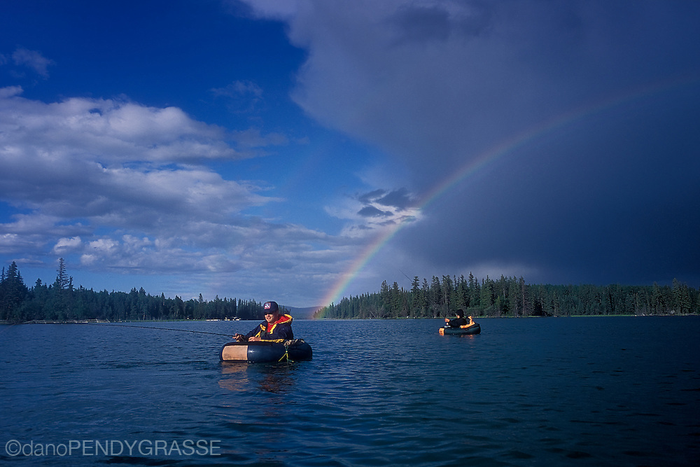 A rainbow crosses the sky over flyfishermen in their float tubes on a lake in British Columbia, Canada.