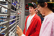 "24 NOVEMBER 2011 - PHOENIX, AZ: Jack Nudo (CQ LEFT RED SHIRT), from Scottsdale, 17, Jake Flick (CQ BACKGROUND BETWEEN THE TWO), 17, from Glendale, and Drew Tsao, 17, (CQ RIGHT PINK SHIRT) from Scottsdale wait for the Game Stop to open at Paradise Valley Mall Thursday. ""Black Friday,"" the unofficial start of the holiday shopping season started even earlier than normal. Many stores, including Target and Best Buy, opened at midnight.    Photo by Jack Kurtz"