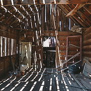 Old abandoned wooden shack. The walls and roof have holes and large gaps between the timbers and the building has no front door. The paint is weathered and peeling. The building is in Thompson Springs, Utah.
