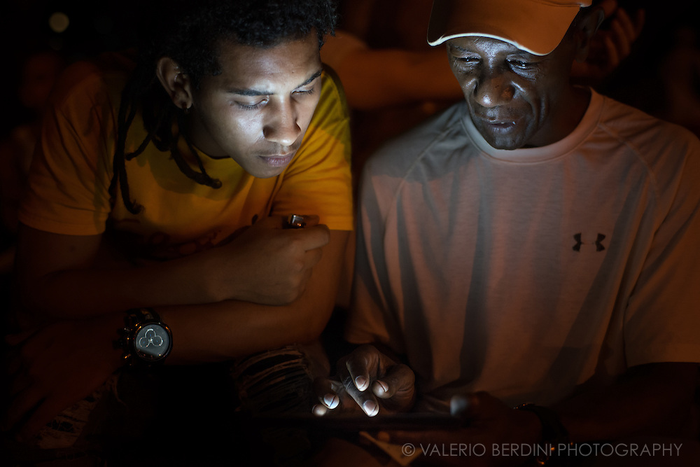 Two men log in an ETECSA wi-fi hotspot in Parque Fe del Valle in Havana de Cuba, on the evening of 29 December 2015. In order to connect to the Internet through wi-fi spots, a card at the cost of $2 per hour is needed. The price is prohibitive for most Cubans that do not have access to the convertible pesos, the currency used by tourist and foreigners. These men were aware of the photographer, but they continued in their activity. This photo was not staged.<br />
