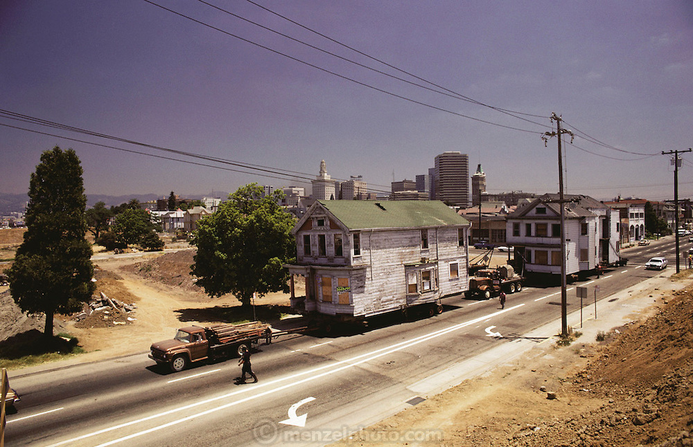 Moving two large two story houses for urban renewal in Oakland, California, 1979.