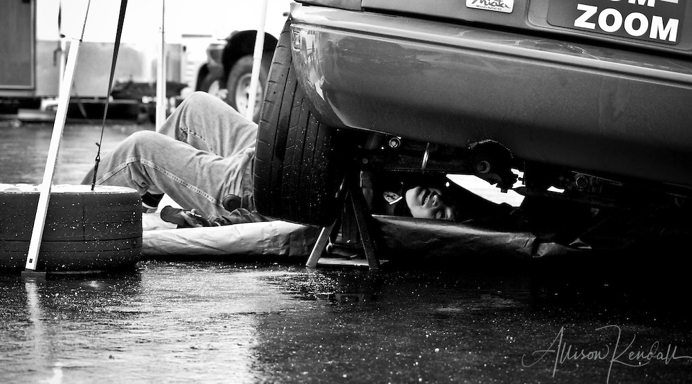 A mechanic works under a Miata during an SCCA racing event at Laguna Seca