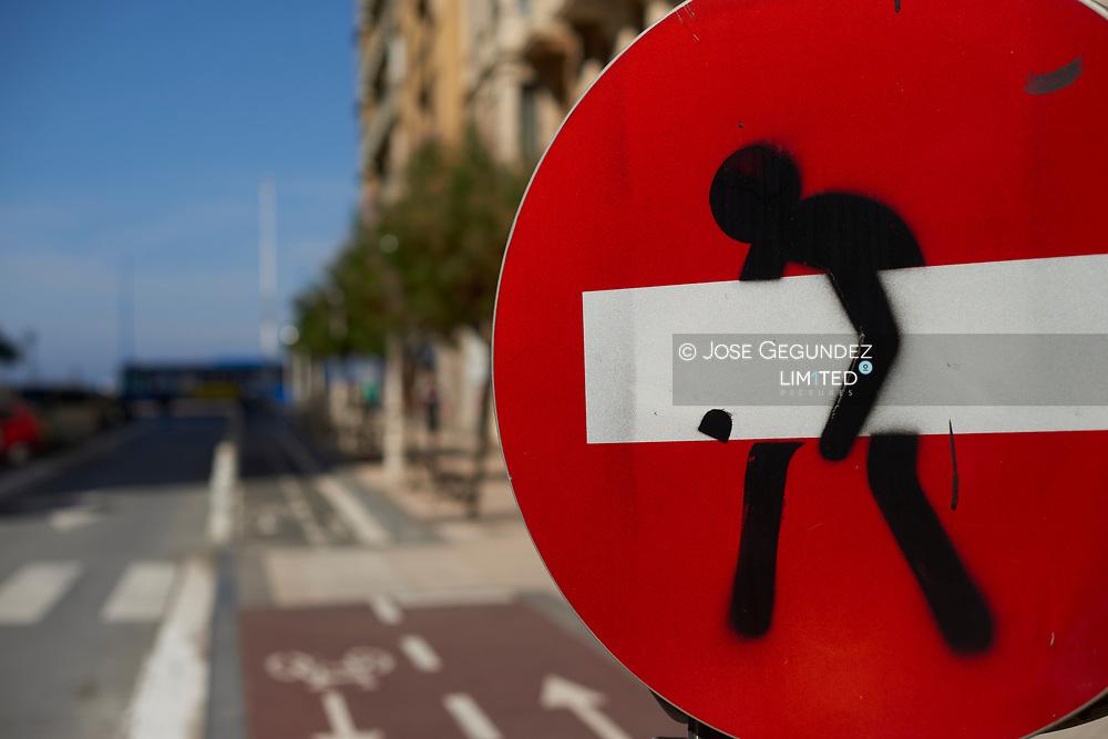 Forbidden direction signal with graffiti. Zurriola Beach