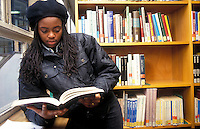 Young black woman researcing in the university library.