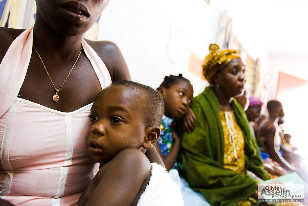 Sixteen-month-old Emmanuel Ngora Kwame sits on his mother's lap while they wait to see a doctor at the NDA health center in Dimbokro, Cote d'Ivoire on Friday June 19, 2009.