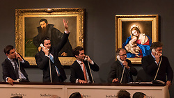 "© Licensed to London News Pictures. 07/12/2016. London, UK. Sotheby's staff make bids on behalf of telephone clients in front of (L to R) ""Portrait of an architect"" by Lorenzo Lotto which sold for a hammer price of GBP340k (est. GBP 200-300k) and ""Madonna and Child"" by Giovanni Battista Salvi, called Sassoferrato which sold for a hammer price of GBP100k (est. GBP 60-80k),  at the Old Masters Evening Sale at Sotheby's in New Bond Street. Photo credit : Stephen Chung/LNP"
