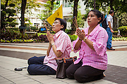 26 NOVEMBER 2012 - BANGKOK, THAILAND:   Women pray for the hospitalized King of Thailand in the courtyard at Siriraj Hospital, outside the wing housing the King of Thailand, in Bangkok. Siriraj was the first hospital in Thailand and was founded by King Chulalongkorn in 1888. It is named after the king's 18-month old son, Prince Siriraj Kakuttaphan, who had died from dysentery a year before the opening of the hospital. It's reported to one of the best hospitals in Thailand and has been home to Bhumibol Adulyadej, the King of Thailand, since 2009, when he was hospitalized to treat several ailments. Since his hospitalization tens of thousands of people have come to pay respects and offer get well wishes. The King's 85th birthday is on Dec 5 and crowds at the hospital are growing as his birthday approaches. The King is much revered throughout Thailand and is seen as unifying force in the politically fractured country.      PHOTO BY JACK KURTZ