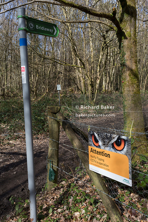 A bridleway landscape and a sign warning fly-tippers of CCTV coverage on a rural lane in Kent, on 19th March 2019, in Westerham, England.