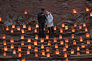 A couple looks at the ruins of the San José de los Jémez Mission part of the Jemez Historic Site is illuminated by hundreds of small paper lanterns known as luminaria to celebrate the holiday season December 12, 2015 in Jemez Springs, New Mexico. The site is in the Jémez Indian pueblo and contains an early 17th-century mission complex.