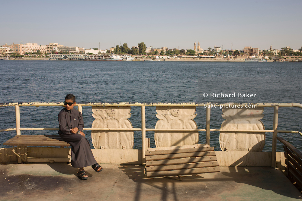 A young boy sits on the top deck of the state-run ferry across the River Nile at Luxor, Nile Valley, Egypt.