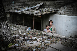 Mother with her daughter breathe the fresh air standing on the stairs leading to the shelter during rocket fire break in Ilovaysk, some 50km from Donetsk, eastern Ukraine, 14 August 2014. Parts of Ilovaysk were destroyed by Ukranian army's shelling. According to reports, more than two thousand people live in shelters without water, electricity and food.