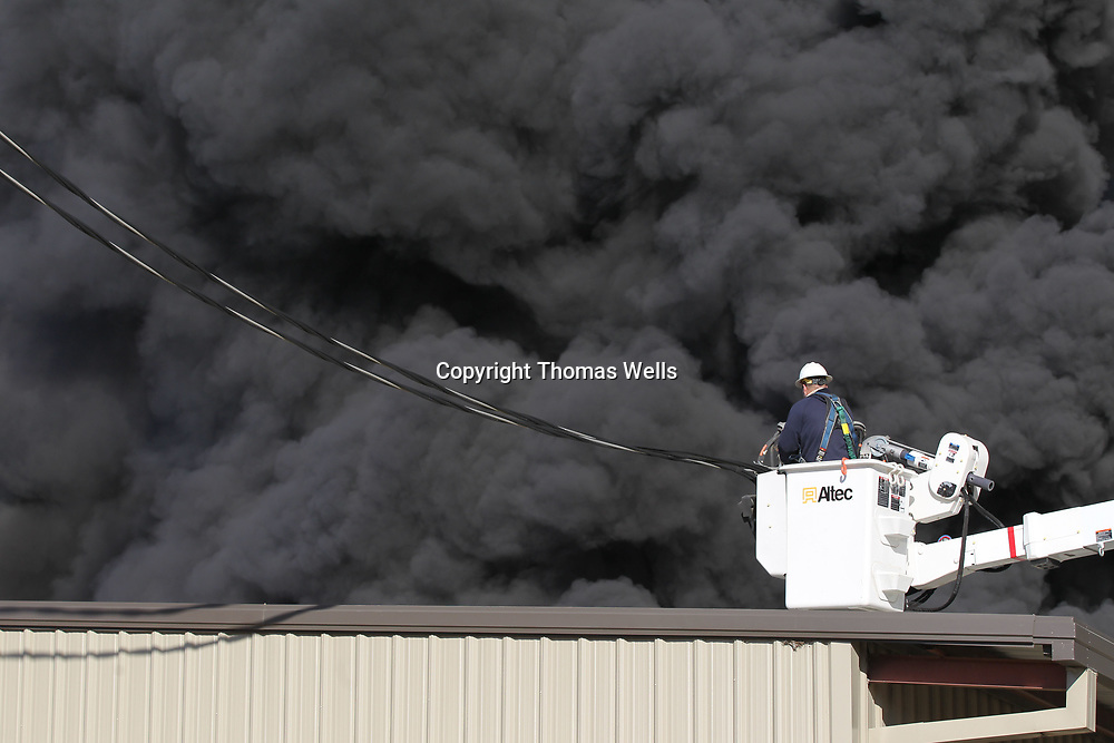 Pontotoc Power employee Tyler Parker watches the nearby flames break through the roof at American Furniture as he disconnets the lines from the plant on Friday in Ecru.