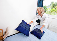 Senior woman setting up cushions on bed at home