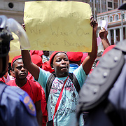 Surrounded by policemen, EFF members protest outside the Legislature during the delivery of SOPA speech. Among their claims, they demand<br />  the right to occupy vacant land in Gauteng and build houses for the people.