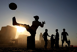 Local children playing football on the beach in Durban