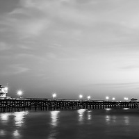 Black and white panorama photo of San Clemente pier at sunset. San Clemente California is a beach city along the Pacific Ocean in the Western USA. Copyright ⓒ 2017 Paul Velgos with All Rights Reserved.