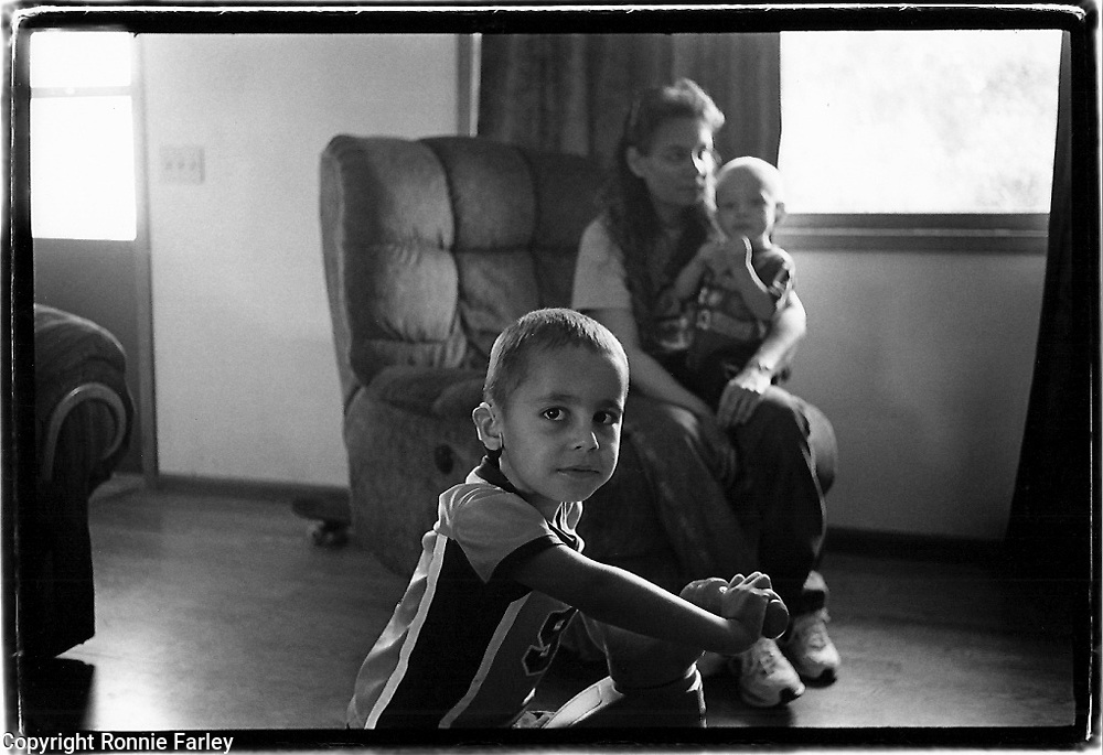 Willie Clifford rides his big wheel while his grandmother Jonnie holds his brother Carter, Pine Ridge Reservation, Kyle, South Dakota, 2007