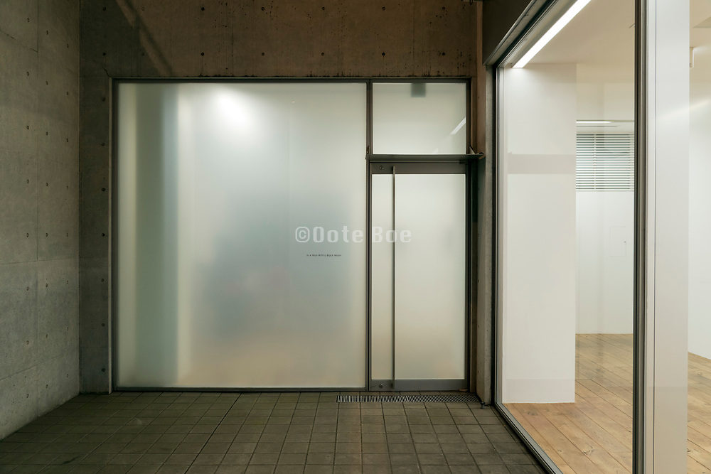 large glass wall with door lighted during night time