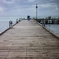 Wooden jetty with people looking out to sea