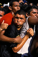 """A man struggles to keep one hand on """"la corda"""", the rope."""