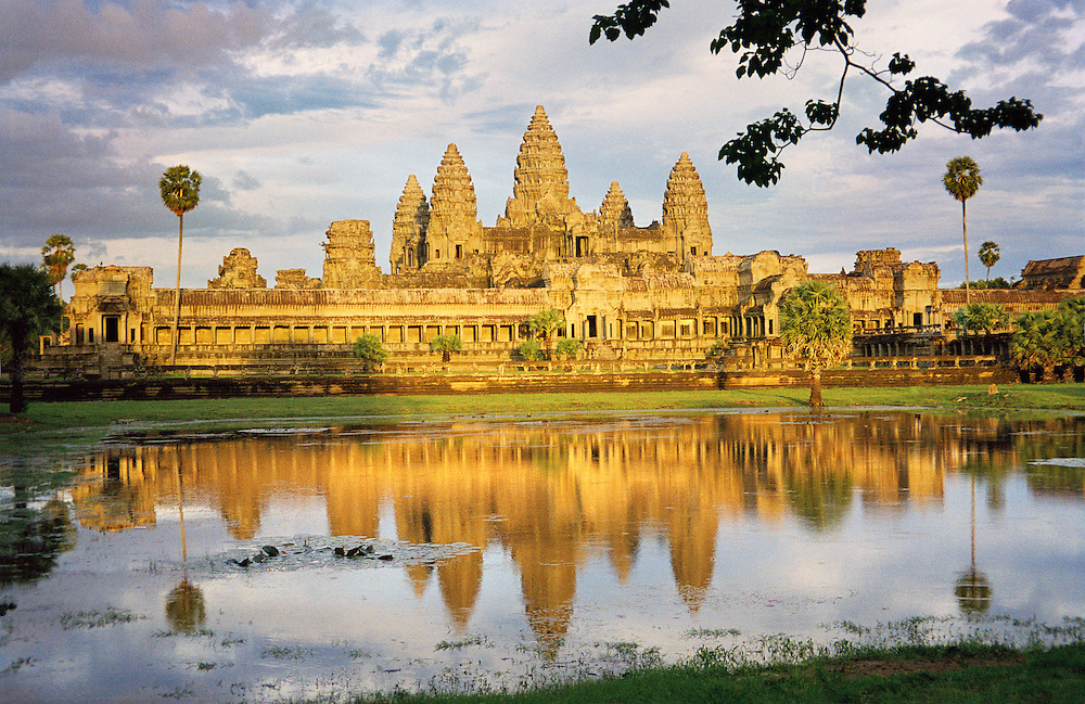 As the largest religious structure ever built and proprietor of some of the world&rsquo;s most magnificent stone carvings, Angkor Wat is considered by many to be one of the greatest architectural achievements in human history. Divided into the three main levels of the Hindu cosmos, it features an 800 meter long gallery of magnificent bas-reliefs depicting epic stories from Hindu mythology, four stone block swimming pools and five central towers. These towers depict the peaks of Mount Meru, home of the gods and the center of the Hindu universe. At over 180 feet high, they can not only be seen from the town of Siem Reap six kilometers away, they can also be seen all over the country as the main symbol on the Cambodian flag.<br /> The Wat is the crowning achievement of the Khmer civilization which, in it&rsquo;s prime, ruled over most of Southeast Asia. It was commissioned by and built for the god-king, Suryavarman II who was worshipped as an incarnation of the protector god Vishnu. The only temple in the Khmer empire facing West into the setting sun, a symbol of death in Hinduism, it is an accepted belief that it was built as a mausoleum for Suryavarman II. The fact that it took 50,000 artist and laborers nearly 40 years to complete is a testament to the Khmers power, wealth and devotion.<br /> To make this photograph showing all five towers, I walked off of the main causeway and joined the cattle that still graze in the fields contained within Angkor&rsquo;s vast complex. Taken just before sunset, it illustrates why we photographers refer to this time of day as &ldquo;golden hour&rdquo;. Taken at any other time of the day, the wat wouldn&rsquo;t have this beautiful golden color of the sunset, but rather it&rsquo;s natural stone-grey color.