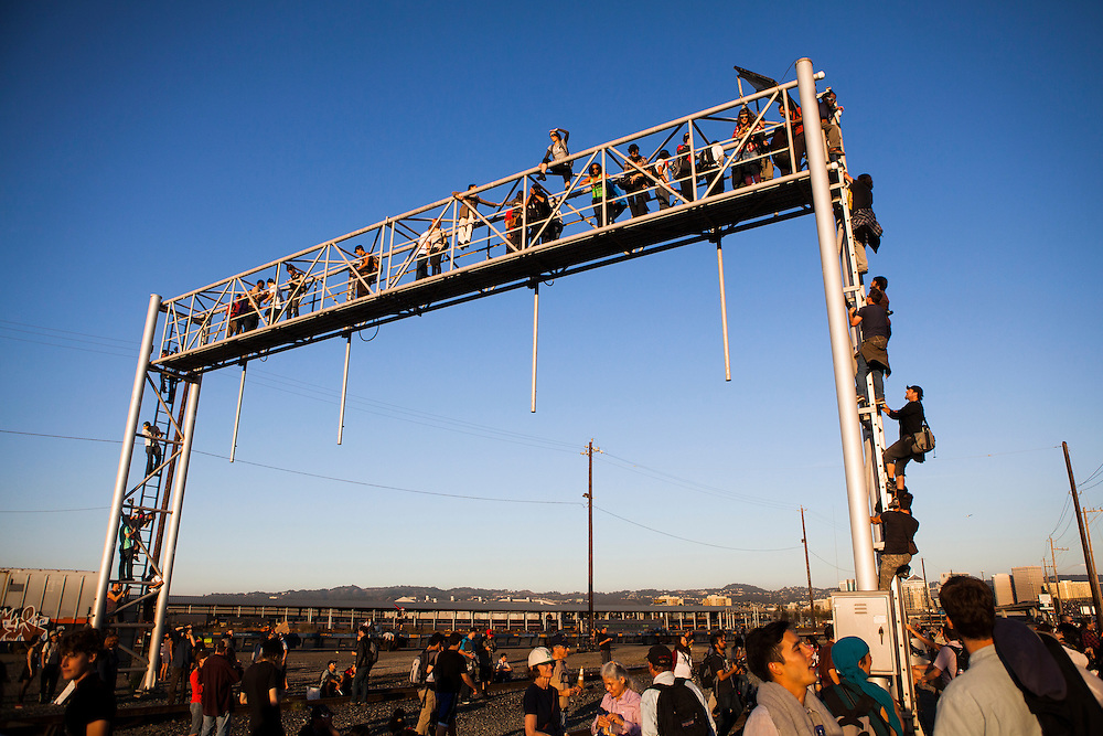 OAKLAND, CA - NOVEMBER 2, 2011: Occupy protesters ciimb atop a railway structure during their shutdown of the Port of Oakland.