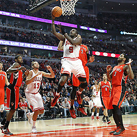 24 March 2012: Chicago Bulls small forward Luol Deng (9) goes for the layup past Toronto Raptors small forward James Johnson (2) during the Chicago Bulls 102-101 victory in overtime over the Toronto Raptors at the United Center, Chicago, Illinois, USA.