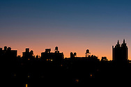 A silhouetted view of the Manhattan skyline including the San Remo building on the Upper West Side at sunrise;  New York City, New York State, U.S.A.