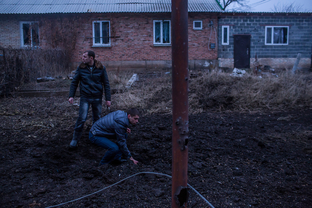 ARTEMIVSK, UKRAINE - FEBRUARY 14: Men examine the crater caused by an artillery strike on February 14, 2015 in Artemivsk, Ukraine. A ceasefire between Ukrainian forces and pro-Russian rebels is scheduled to go into effect at midnight. (Photo by Brendan Hoffman/Getty Images) *** Local Caption ***