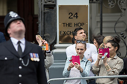© Licensed to London News Pictures. 10/04/2017. London, UK. Members of the public take photographs as a policeman looks up to the sky during the funeral of PC Keith Palmer at Southwark Cathedral. PC Palmer was stabbed to death at the entrance to Parliament by Khalid Masood on 22 March 2017. Masood also drove a vehicle into people on Westminster bridge, killing four. Photo credit : Tom Nicholson/LNP