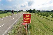 Nederland, Varik, 9-6-2018Buurtbewoners , inwoners van de dorpen Varik en Heesselt, hebben als protest borden en een spandoek langs de dijk geplaatst waarop ze hun kritiek uiten op de voorgenomen aanleg van een watergeul om de dorpen heen . In het kader van de bescherming tegen het water moeten hier nog besluiten over genomen worden . Dijkversterking, dijkversteviging, .