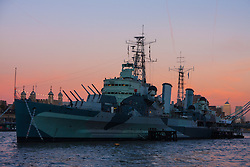 London, November 24th 2014. With London having enjoyed a clear if cold day, weather forecasters are predicying a cold night with temperatures expected to dip as low as 3 degrees in the early hours of Tuesday. PICTURED: the evening sky turns pink behind HMS Belfast.