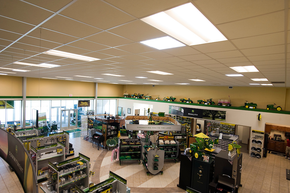 "Greensburg, Kansas, USA..BTI-Greensburg John Deere dealership has 12 tubular daylighting devices in the retail space...BTI-Greensburg has built a new John Deere Dealership and Service shop in Greensburg, Kansas. The dealership is designed to be fully daylit using 24 skylights in the service shop and 12 tubular daylighting devices in the retail space. Well insulated metal wall panels - commonly used in refrigerated warehouses - have an assembly R-value of R-16 and eliminate thermal breaks typically seen in metal building construction. The high bay overhead doors include R-14 insulated panels. R-38 roof insulation incorporates thermal blocks to minimize the thermal breaks at the roof structure. A high efficiency 16 SEER VAV provides heating, cooling, and outdoor air to the retail space, combined with CO2 demand controlled ventilation. Hot water is provided with a combination of a waste oil boiler and natural gas boiler. Waste oil from oil changes in the service shop is stored on-site and used during the winter to offset natural gas use. Radiant slab heating minimizes heat loss during the frequent bay door open and close cycles. Two wind turbines (4.2 kW and 1.9 kw) provide electricity to the facility, offsetting an estimated 8% of the building load. The metal building has been certified LEED Platinum at approximatly 50% energy cost savings...""Greensburg: Better, Stronger, Greener!"".On May 4, 2007, an EF5 tornado cut a 1.7-mile path of destruction through Greensburg, Kansas. Winds reaching speeds of 205 miles per hour uprooted trees, demolished homes and leveled the town. Eleven people died and 95% of the buildings were destroyed beyond repair. Residents have since worked furiously to rebuild it in a way that is both economically and environmentally sustainable and to meet the highest environmental standards. Greensburg, whose population has dropped from about 1400 to 800 following the storm and is now growing again, is currently the greenest town in America and the fi"