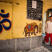 "A Hindu priest leaves a temple that is adorned with the Hindi script for OM said to be ""the sound of the universe."""