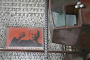 """Lenin ruft in einer Maschinenbaufabrik zum Sieg. Südossetien erklärte sich 1990 selbsständig und konnte den folgenden Sezessionskrieg gegen die Georgier für sich entscheiden. Zwischen Georgien und der abtrünnigen Region, die den Anschluß an die Russische Förderation fordert, kommt es trotz des Waffenstillstandsabkommens von 1992 immer wieder zu bewaffneten Ausseinandersetzungen. (Lenin calls for victory insight a factory. South Ossetia is a de facto independent republic located within the internationally recognized borders of Georgia. Although this former Soviet autonomous region has declared its independence in 1990. After the following civil war between georgians and ossetians ends in 1992, most parts of the territory is ossetian controlled, while some villages with georgian population are administrated by an georgian """"Alternative Government"""".)"""