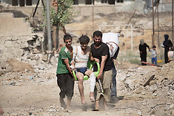&copy; Licensed to London News Pictures. 15/06/2017. Mosul, Iraq. Mosul residents carry an injured man across open ground, under constant threat of being shot by ISIS snipers, as they escape Islamic State territory to reach Iraqi Army positions.<br /> <br /> Despite heavy fighting between the Islamic State and Iraqi Security Forces many civilians have started to leave ISIS territory in West Mosul. Mosul residents, many of whom have been in hiding in their homes since the start of the West Mosul Offensive, often have to run through ISIS sniper and machine gun fire to reach the safety of Iraqi Security Forces positions. Photo credit: Matt Cetti-Roberts/LNP
