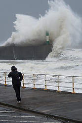 "© London News Pictures. 08/02/2014. Aberystwyth, UK. <br /> A woman walking in Gale force winds as giant waves strike the lighthouse at Aberystwyth, Wales at high tide. The winds are forecast to strengthen throughout the day, gusting up to 70 or 80 mph, and with the rising tide, their impact could be potentially damaging again. An amber ""be prepared"" warning  has been issued by the Met Office for wind,. Photo credit: Keith Morris/LNP"