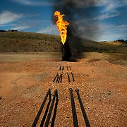 Natural gas flare burns off a rig outside of Trenton, North Dakota. The oil boom is redrawing North Dakota's landscape and creating opportunity for thousands of unemployed Americans. However, the economic prosperity has exacerbated problems in housing, infrastructure and traffic...Known for the beauty of its great plains, North Dakota has long been the least populated state in the country. Because of the Bakken oil boom, everyday, mostly men, pour in from across the nation looking for work. The small town of Williston has exploded as a result. Ten years ago Williston, North Dakota was a quiet agricultural town with a population around 12,000. In a decade the population has more than doubled to over 30,000. More than half of Williston's residents now work in oil-related jobs and the city's unemployment rate is at 1 percent, which is the lowest in the U.S...