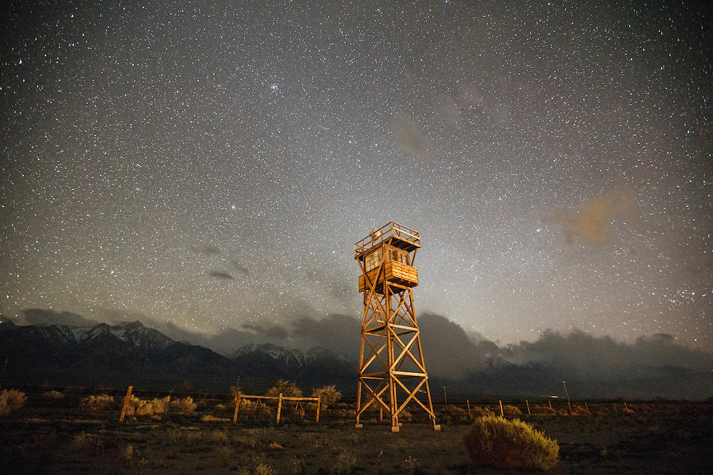 A long exposure photograph shows a reconstructed guard tower as it stands on the perimeter fence while stars shine in the night sky at the Manzanar National Historic Site on the eve of the 47th Annual Manzanar Pilgrimage on Friday, April 29, 2016 in the Owens Valley of Inyo County, Calif. Now a National Historic Site, the Manzanar War Relocation Center was one of ten camps where Japanese American citizens and resident Japanese aliens were interned during World War II. Photo by Patrick T. Fallon / Special to the National Parks Conservation Association