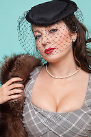 Portrait of beautiful young woman with fur boa and veiled hat against blue background