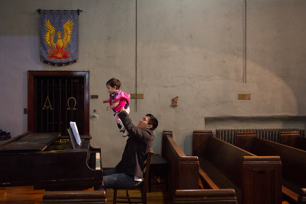 Father and infant play before the start of the Indonesian Lutheran service, Sunday afternoons at St. Mark's Church.