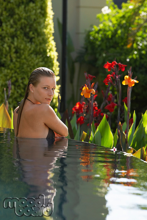 Young woman in natural swimming pool portrait