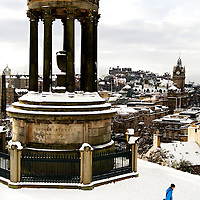 EDINBURGH, UK - 28th November 2010:  A member of the public walks past a monument on Calton Hill with Edinburgh Castle and surrounding rooftops after heavy snow hit the city early on Sunday morning. ..Heavy snow has fallen across large parts of the UK, disrupting travel.  Weather warnings of heavy and drifting snow are also in place for many places across the UK...(Photograph: Richard Scott/MAVERICK)